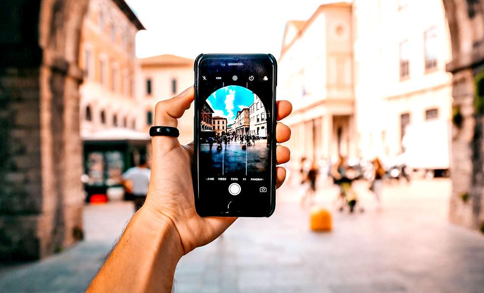 mano che tiene uno smartphone che mostra l'app fotocamera