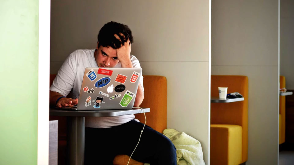 man sitting stressed on laptop