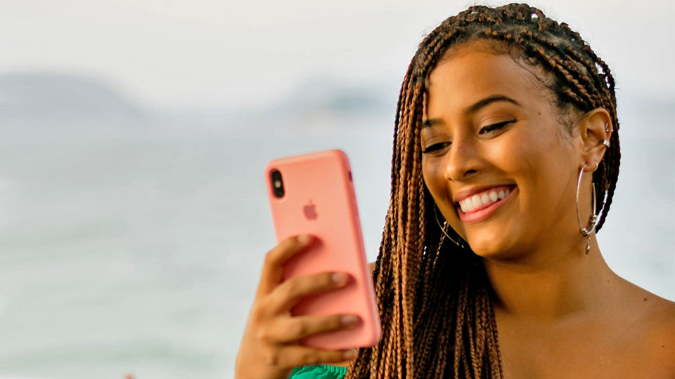 woman holding a pink iphone