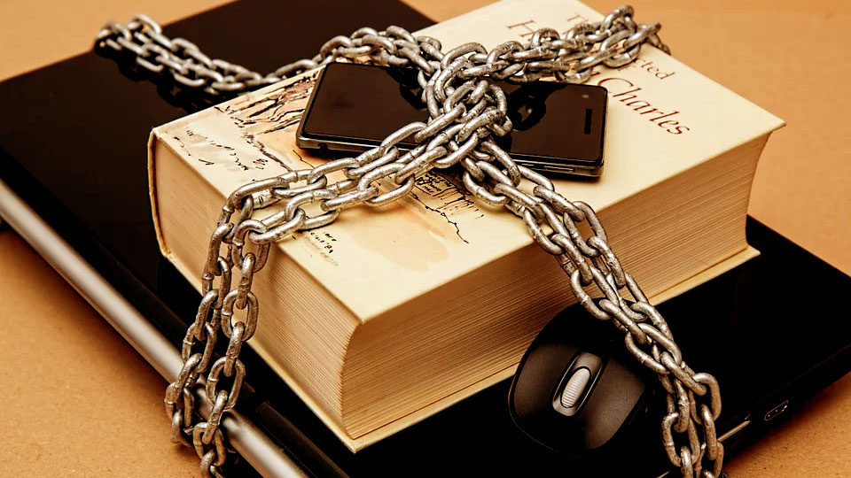 a book, a notebook and a smartphone in chains