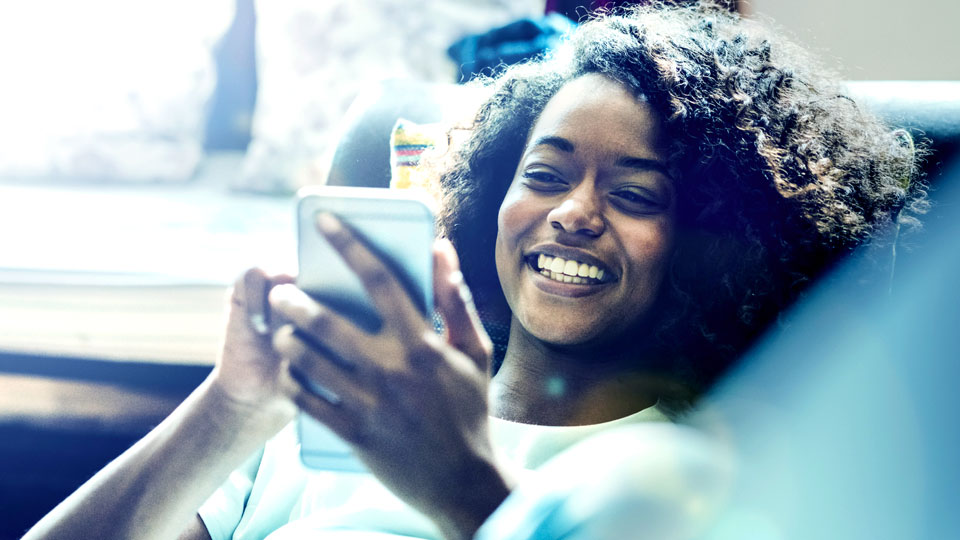 happy black woman holding smartphone