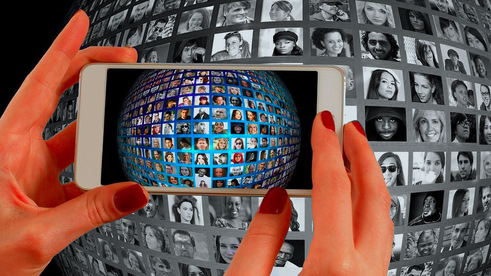 woman hands holding smartphone with many faces and contacts