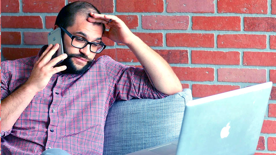 frustrated man holding iphone and looking at laptop