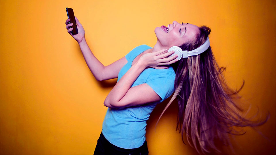 woman holding a phone listening to music with headset