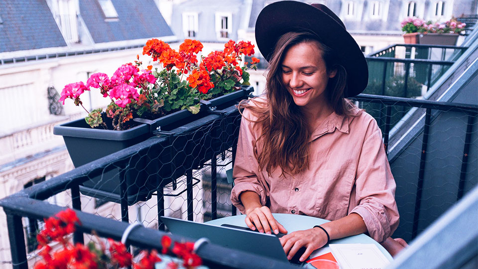 woman sitting on the balcony with flowers looking at her laptop and smiling