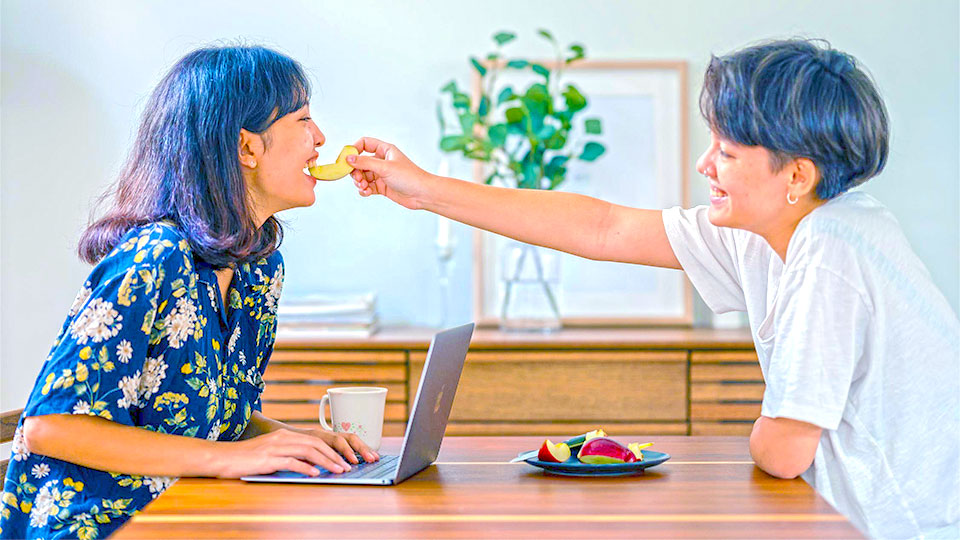 two women at the table smiling and one gives a piece of apple in the mouth of the other woman