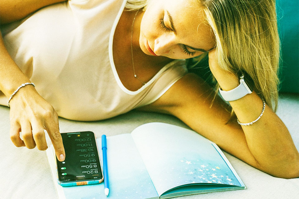 woman is lying on the couch supporting her head with her hand and touching the screen of the smartphone, a pen and a notebook