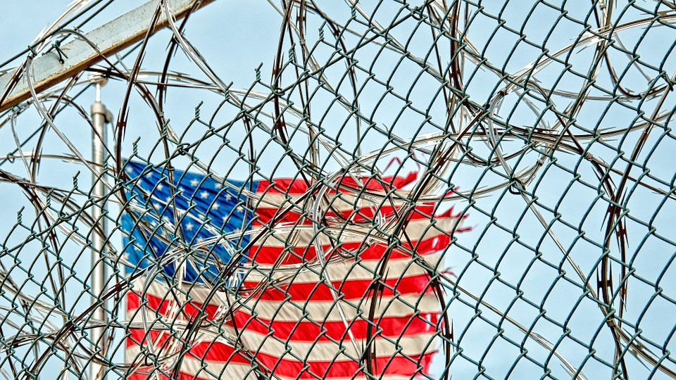 a prison wall with barbed wires and the US flag in the background