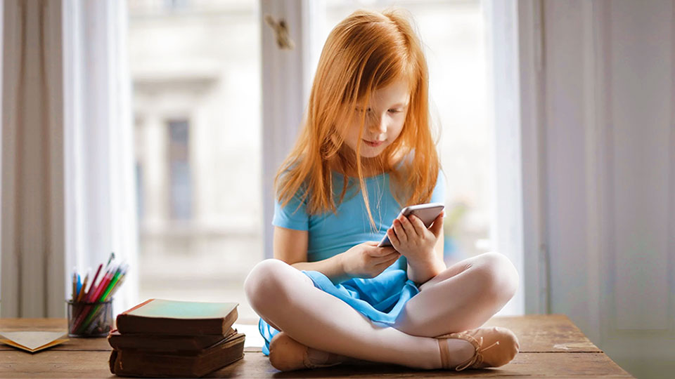 sitting redhead girl holding an iphone