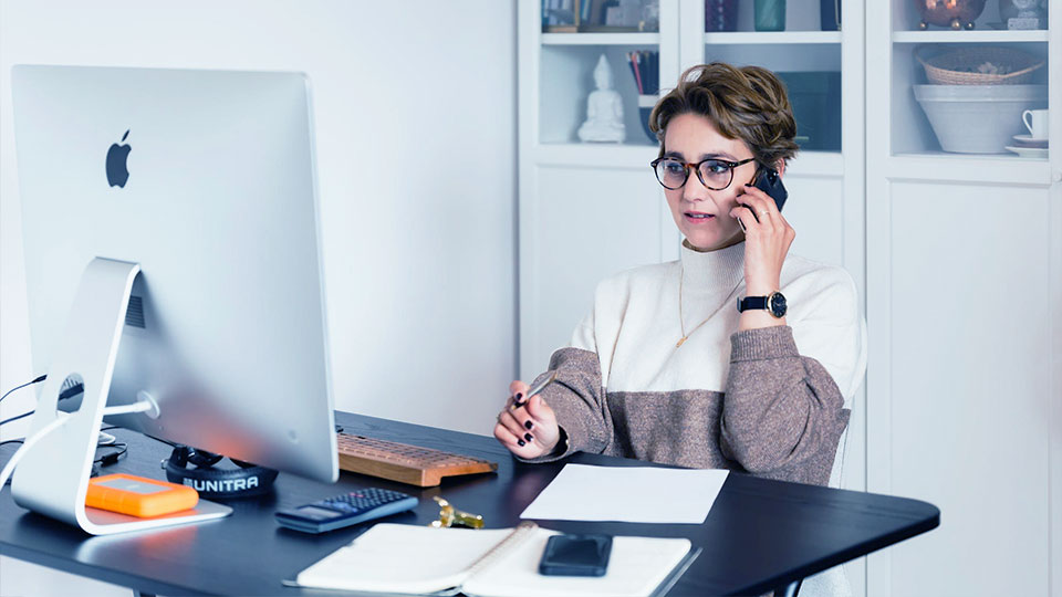 woman at the office desk talking on the phone
