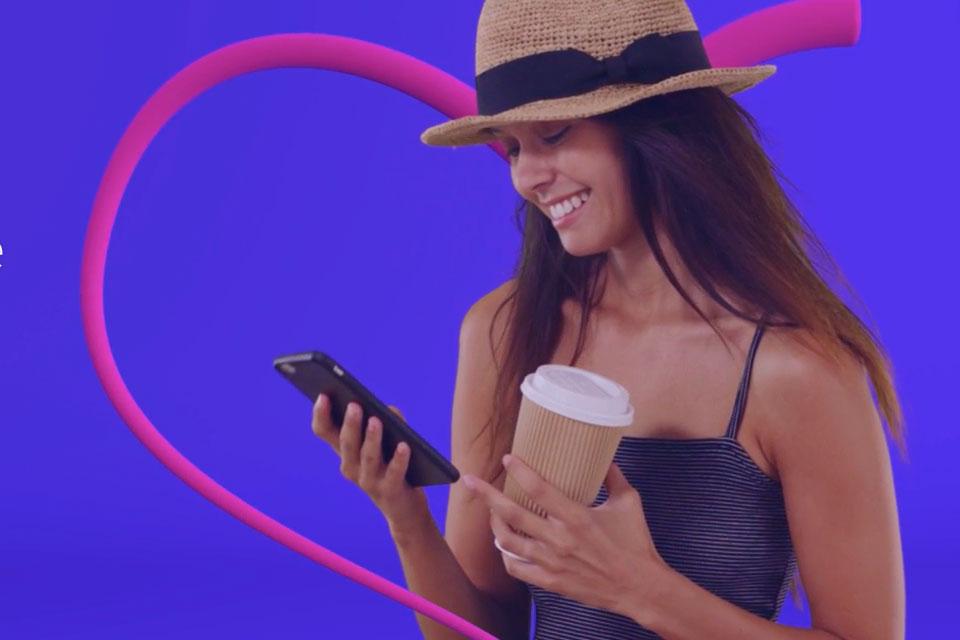 femme avec un chapeau de plage tenant un portable dans une main et un café dans l'autre