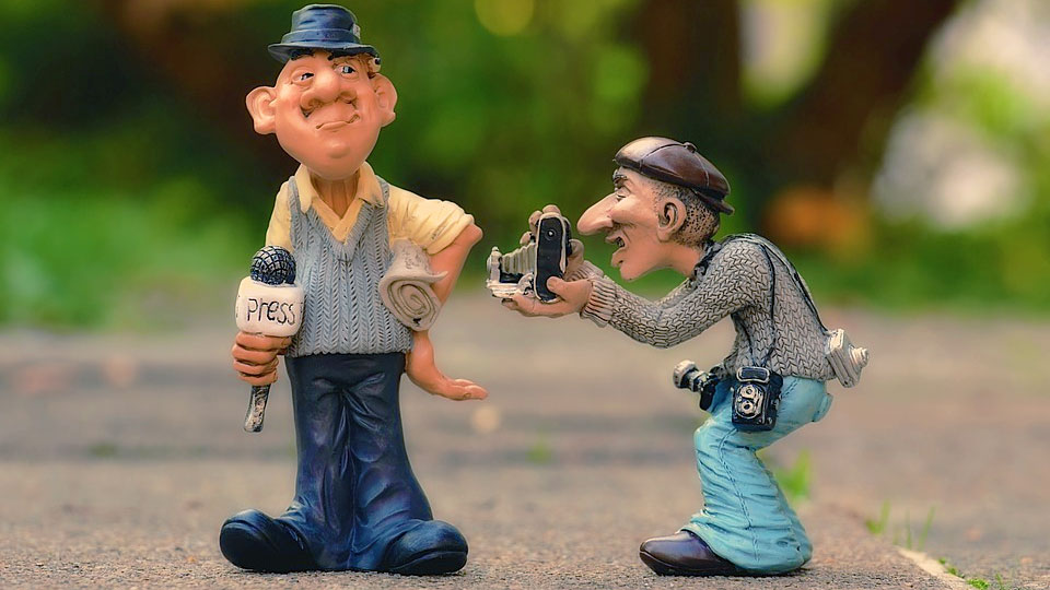 journalist doll with a microphone and another doll with a camera