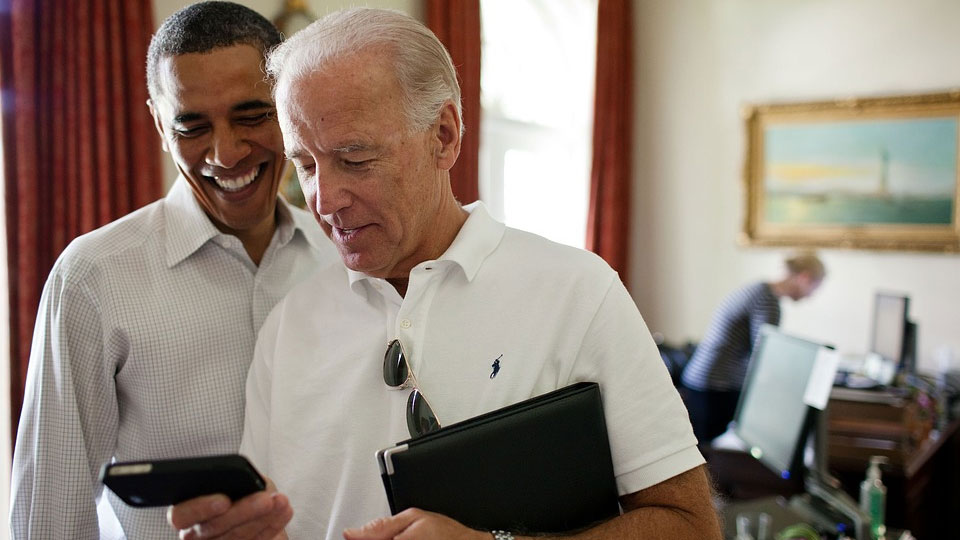 barack obama and joe biden smiling and looking at an iphone