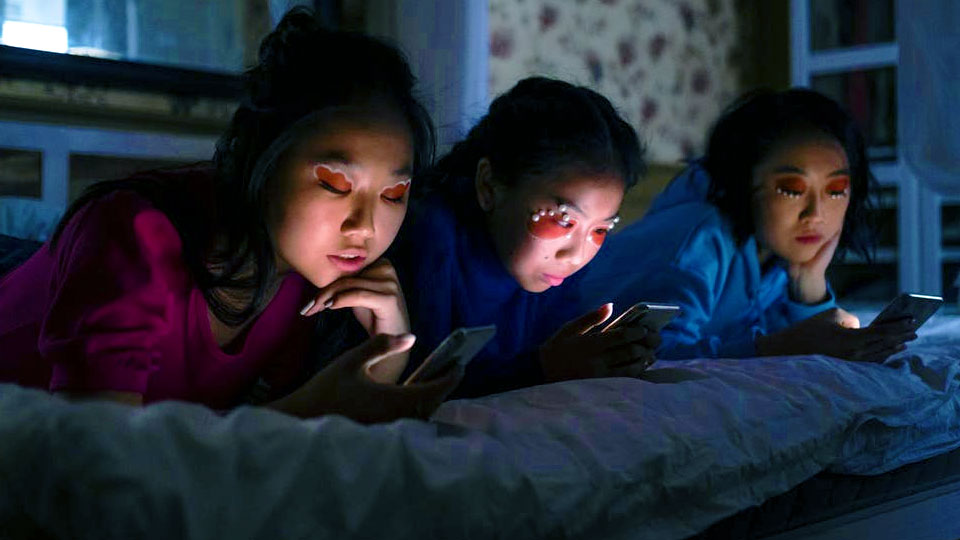 3 girls lying on the bed looking at the smartphone in the dark