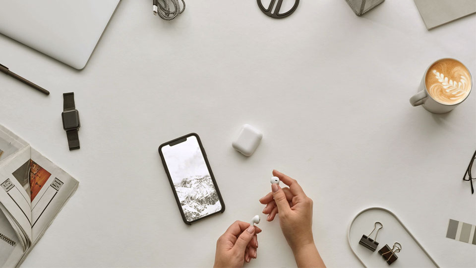 a smartphone on a desk and hands holding earphones