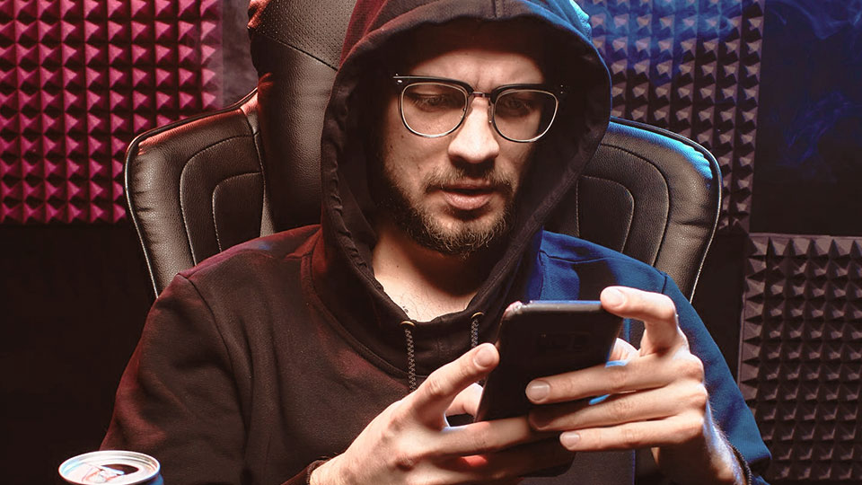 a man with a hoodie sitting looking at his smartphone