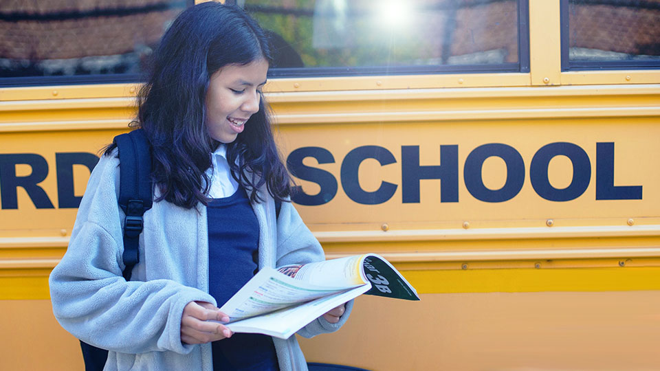 schoolgirl on the side of a school bus looking at a book