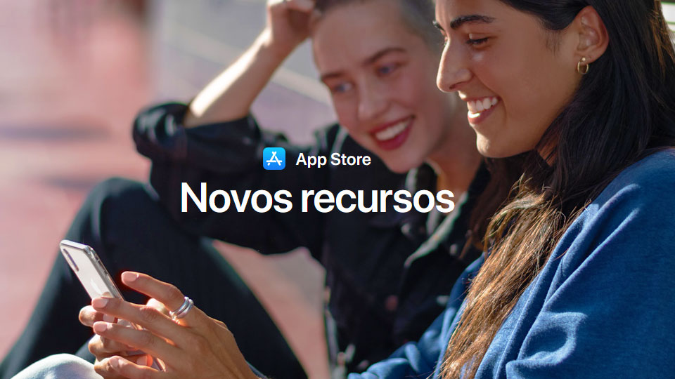 duas mulheres sorrindo e olhando para um iphone