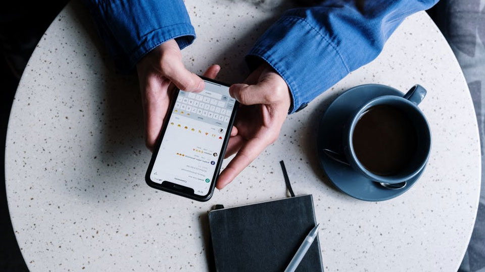 woman's hands holding a iphone on a table with a coffee cup