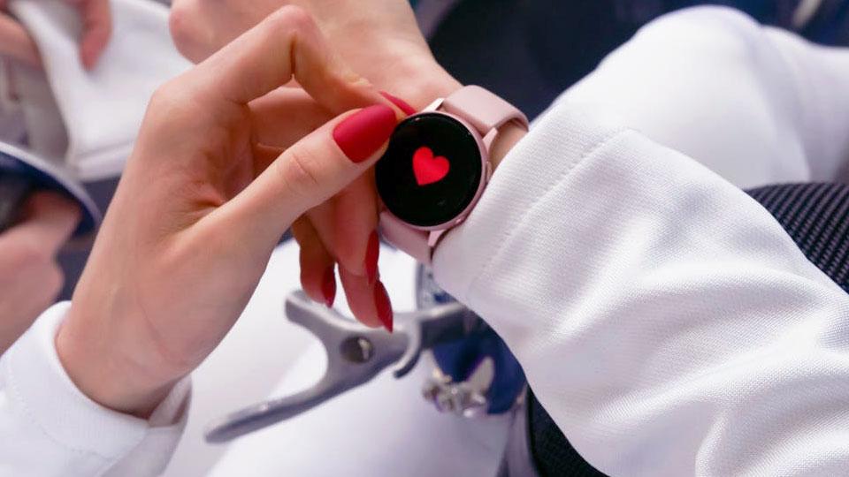 woman's hand touching pink smartwatch