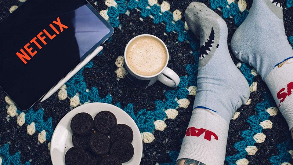 sur le sol, une tablette avec netflix, des cookies, du café et des pieds avec des chaussettes