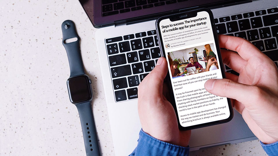 a smartphone showing an article next to a apple watch