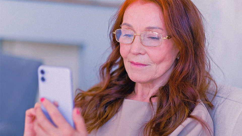 an older woman with glasses looking at her smartphone