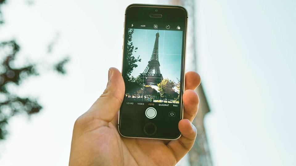 main tenant un smartphone avec une photo de la tour eiffel