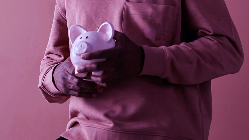man wearing blouse holding a money savvy pig