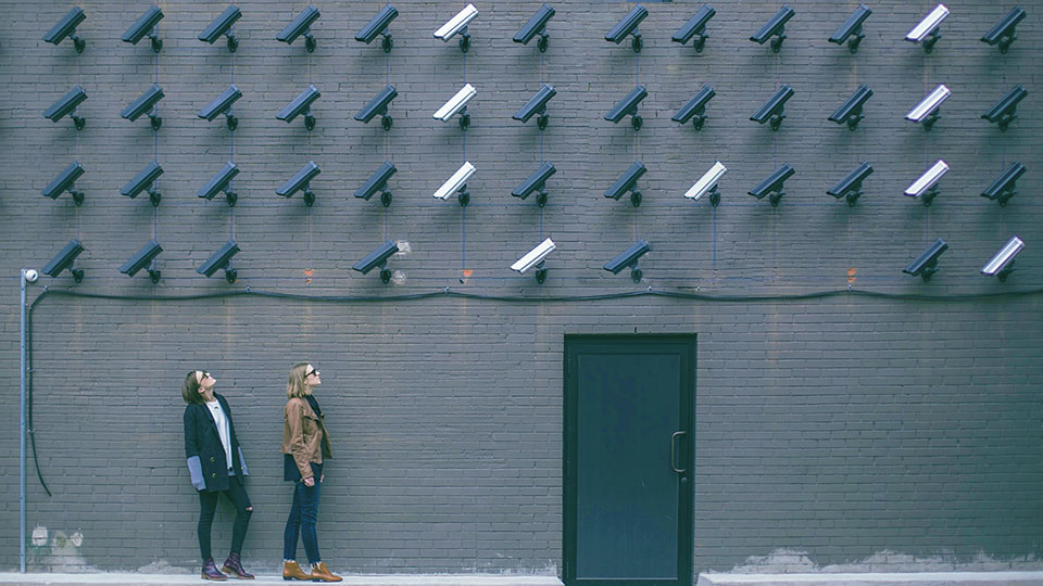 two women on the street looking at a wall full of security cameras