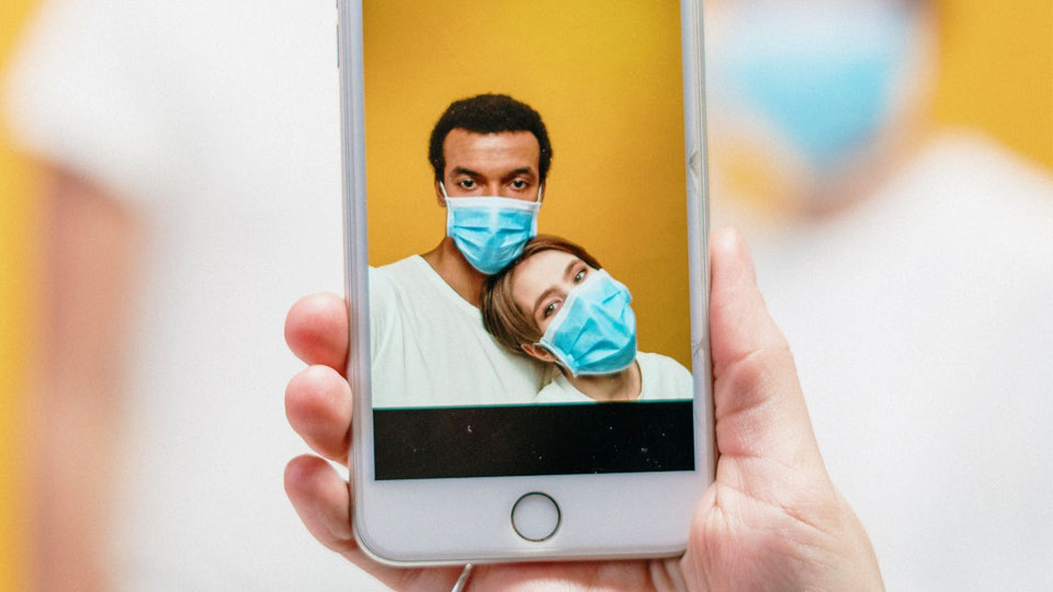 smartphone with photo of people wearing sanitary masks