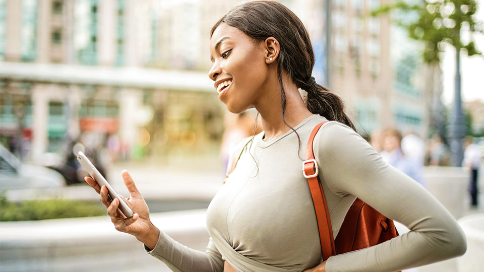 beautiful black woman smiling and looking at her smartphone