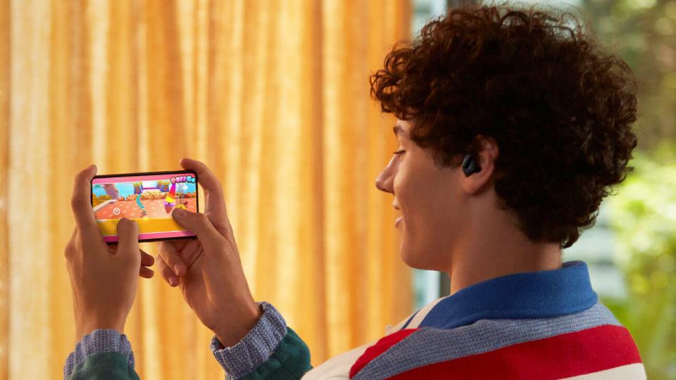 un homme jouant sur son smartphone et ses écouteurs