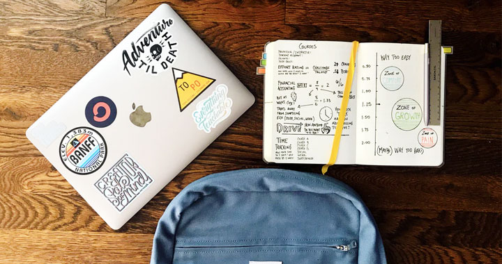 a laptop, a notebook and a backpack on the table