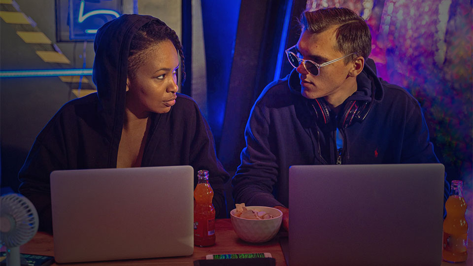 a woman and a man with laptops on the table