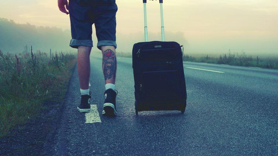 man walking on the road holding black luggage