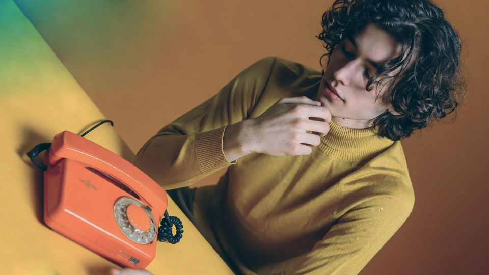 a young man and an orange telephone on the table