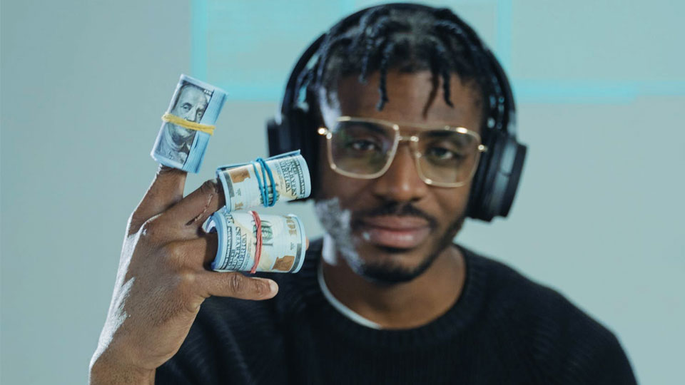 a man with glasses holding dollars in his hand