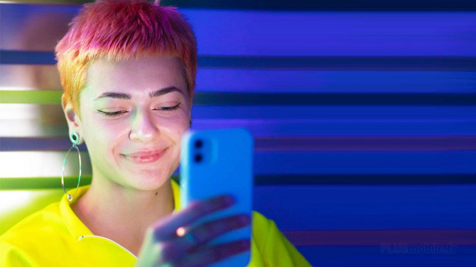 jeune femme souriant et regardant l'écran du mobile
