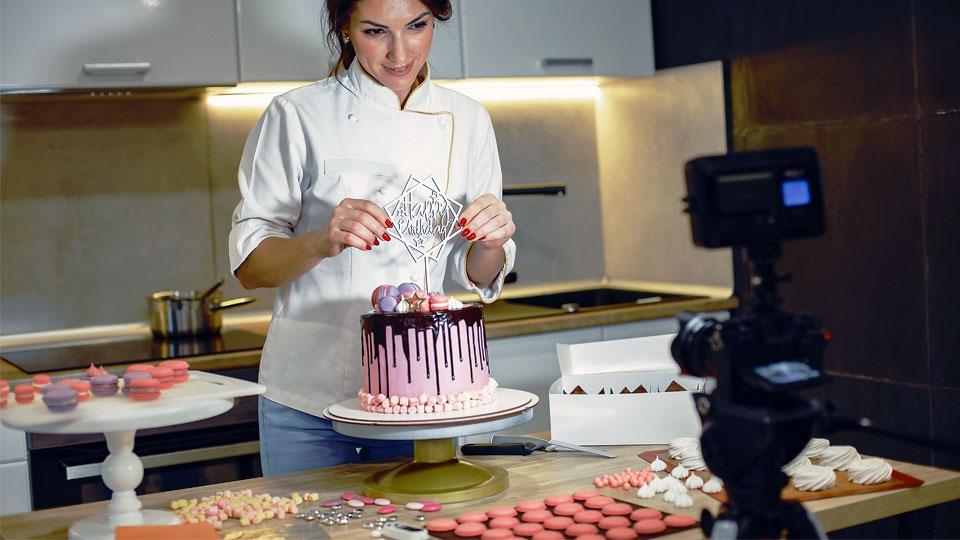 mujer presentando un pastel delante de la cámara