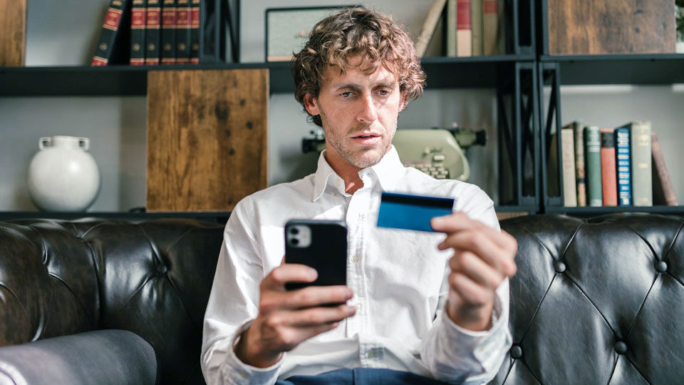 man sitting on sofa holding a credit card and a smartphone